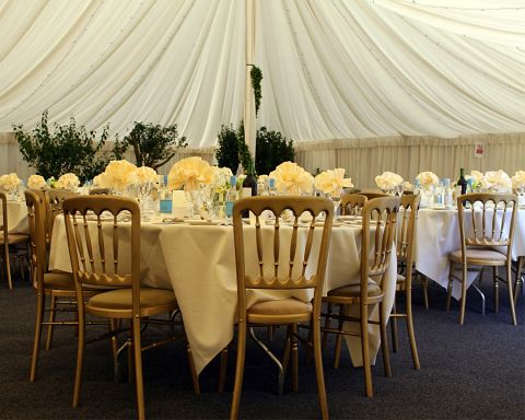 Tables and chairs set out in preparation of a wedding reception
